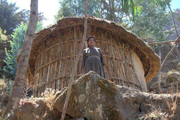 CHICA JUNTO A UN TUKUL CERCA DEL MONASTERIO ASHETAN MARYAM, LALIBELA
